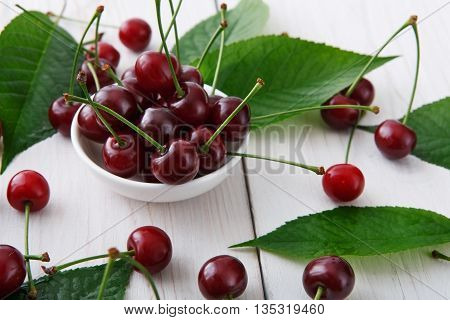 Sweet fresh cherries in bowl with green leaves background. Scattered cherries closeup on white rustic wood. Cherry fruit and leaf backround. Organic cherries at wood table. Food background.