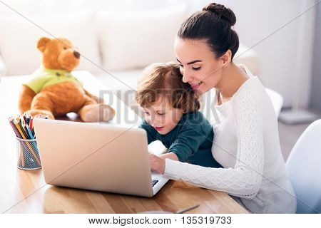 Looking for cartoons. Young delighted woman looking how her son using a laptop while sitting with him at the table