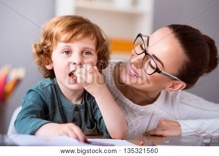 One more piace. Little cute calm boy eating a piece of cake while his smiling beautiful mother looking at him