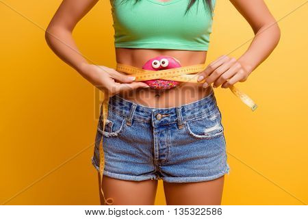 girl holding pink donut near her belly with centimeter. she afraid to be fat poster