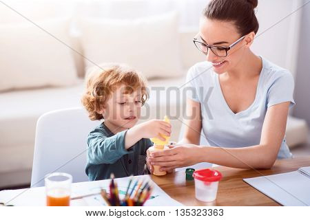 Can I try. Little concentrated boy taking a bottle with soap bubbles while his mother helping him