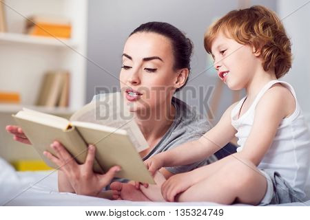 I like this tale. Relaxed contended woman reading a bedtime story for her funny little son