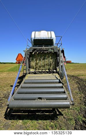 The back of a modern square hay baler where the bale travels down the rollers to meet earth.