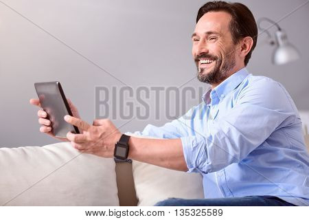 So sincere. Joyful mature man smiling and holding a tablet in front of him while sitting on the couch
