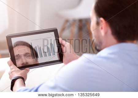 Lets start. Close up of a tablet in hands of a man with some diagrams on the screen
