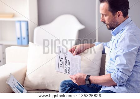 What is new. Serious mature bearded man reading a broadsheet while sitting in front of the laptop with diagrams on the couch