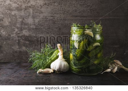 Glass jar of pickled gherkins with dill and garlic on dark metal grey ructic background copy space