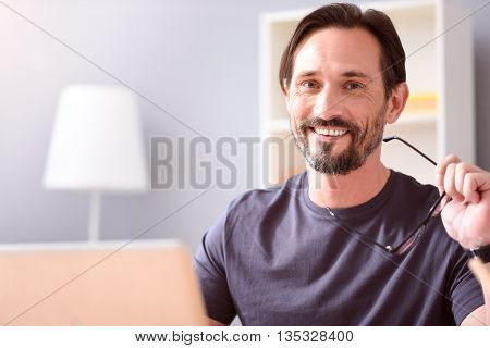 I like what I do. Contented middle aged man holding glasses and looking at the camera while sitting in front of a laptop