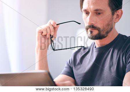 Feeling sad. Gloomy serious mature bearded man holding glasses in his hand while looking at the screen of laptop and sitting at the table