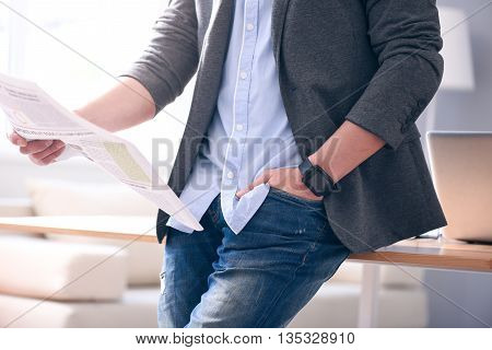 Lets read it. Close up of hands of a man, in one hand he holding a newspaper while the second being in the pocket