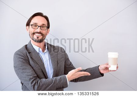 So delicious. Respectable middle aged man pointing with one hand at a cup of coffee while standing isolated on the grey background