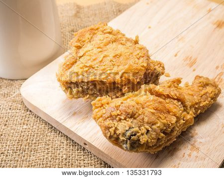 fried chicken on a chopping broad with a glass set on a sack background