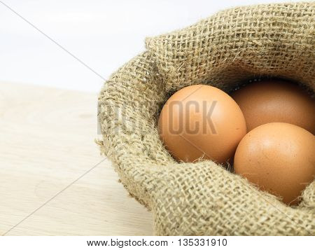 three egg in sack on choping broad background