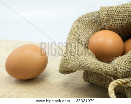 two egg in sackand one on choping broad background