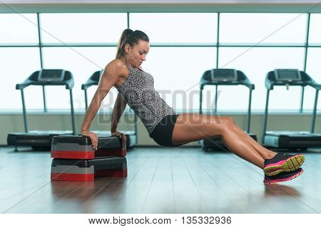 Young Woman Athlete Doing Triceps Exercise On Stepper As Part Of Bodybuilding Training poster