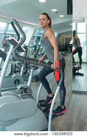 Healthy Women On Elliptical Treadmill In Fitness Gym