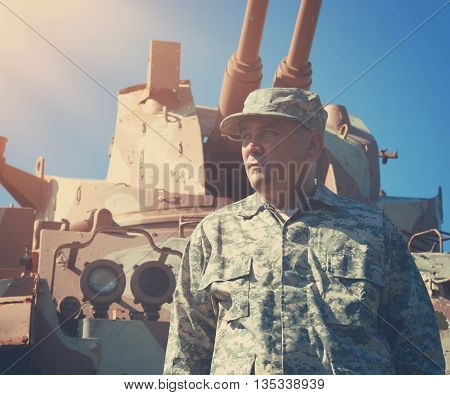 A military soldier is standing in front of an army tank vehicle with sun outside for an american war defense or security concept.