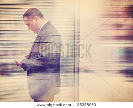 A vintage business man in a suit is texting on his cell phone in the city outside with a blank wall for a communication or message concept.