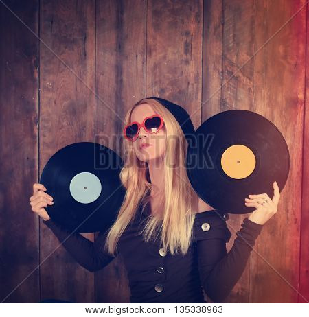 A blonde hipster girl with glasses is holding vintage vinyl records for a music dj or entertainment concept.