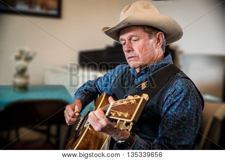Western cowboy is playing guitar for entertainment