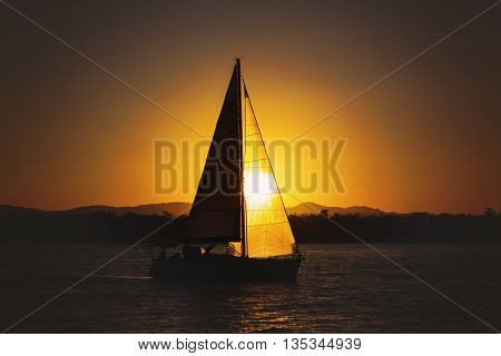 Landscape of Sailing yacht against sun at sunsettime