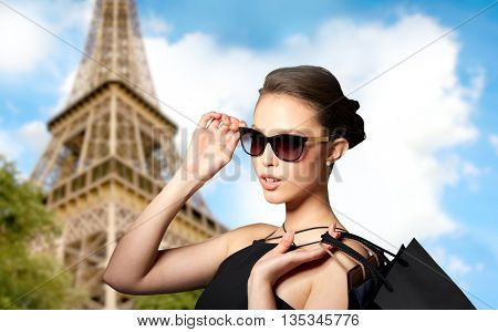 sale, fashion, tour, people and luxury concept - happy beautiful young woman in black sunglasses with shopping bags over paris eiffel tower background