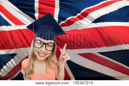 people, graduation and national education concept - smiling young student woman in mortarboard and eyeglasses pointing finger up over english flag