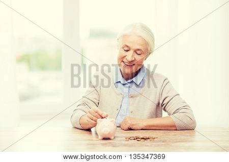 savings, money, annuity insurance, retirement and people concept - smiling senior woman putting coins into piggy bank at home poster