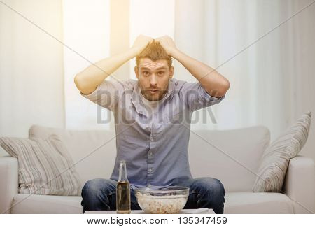 sports, happiness and people concept - sad man watching sports on tv and supporting team at home