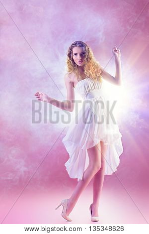 Beautiful romantic girl with wavy foxy hair in light white dress over pink background. Spring look. Ful length portrait.
