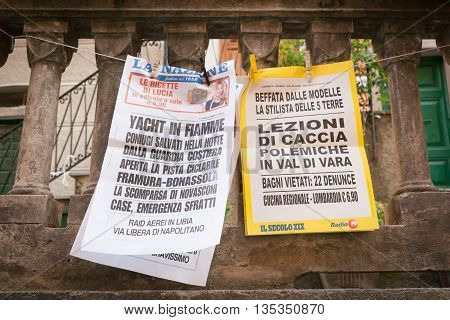 Riomaggiore, Italy, April 27, 2011; Italian newspaper bills strung and clothes peg clipped for villagers to see in Cinque Terre village Riomaggiore