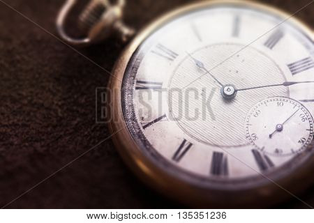 Old pocket watch on grungy leather surface. Shot in low key and extremely shallow depth for impressional feel. Focus is on etching of clock face plate.