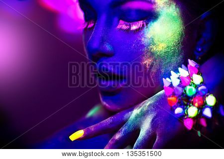 Fashion model woman in neon light, portrait of beautiful model girl with fluorescent powder make-up, Art design of female disco dancer posing in UV, colorful make up. black background