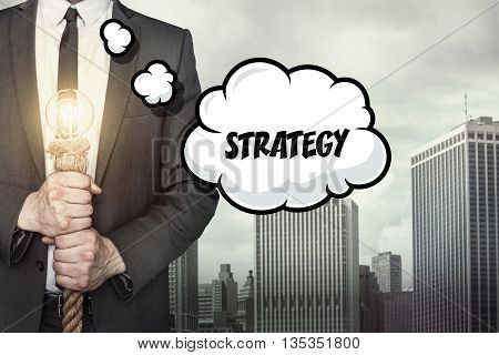 Strategy text on speech bubble with businessman holding lamp on city background