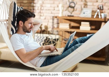 Man resting in hammock at home, using laptop computer. Side view.