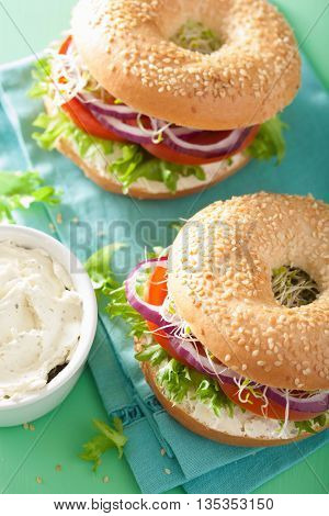 tomato sandwich on bagel with cream cheese onion lettuce alfalfa sprouts