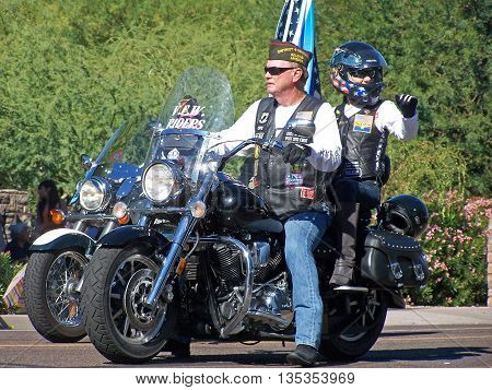 PHOENIX, AZ- NOV. 11: Man with VFW Riders riding a motorcycle with a female passenger wearing a helmet at the Veteran's Day Parade in Phoenix, Arizona on November 11, 2013.