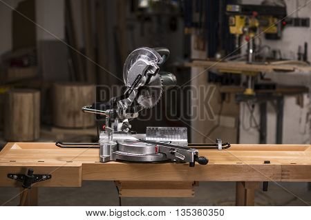 Radial mitre saw on the wooden workbench in carpentry