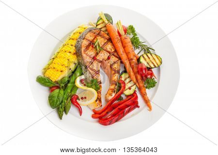 Overhead view of a grilled salmon steak with vegetables corn and asparagus