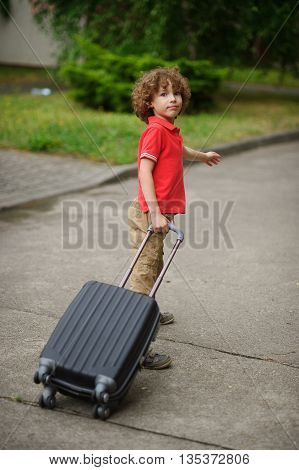 The boy of 8-9 years drags a big suitcase on castors. He stand in a half-turn and looks in the camera with a quiet look. The boy came back home or goes to a way.
