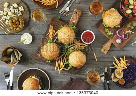 Different burgers with snacks and wine on the wooden table top view. Outdoors food Concept