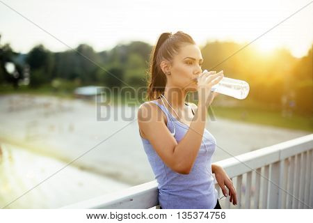 Woman drinking water after running to stay hydrated