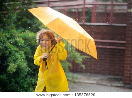 The boy in a bright yellow raincoat to stand under a pouring rain. In hands it squeezes a yellow umbrella. The boy laughs looking in the camera. It likes to walk in the rain.