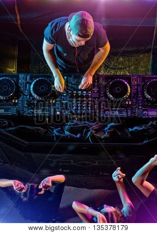 Disc jockey mixing electronic music in club. Shot from aerial perspective. People are dancing