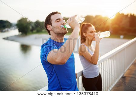Couple staying hydrated after workout on a bridge