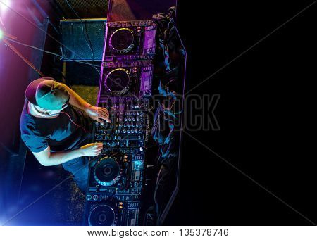 Disc jockey mixing electronic music in club. Shot from aerial perspective. Copyspace for text