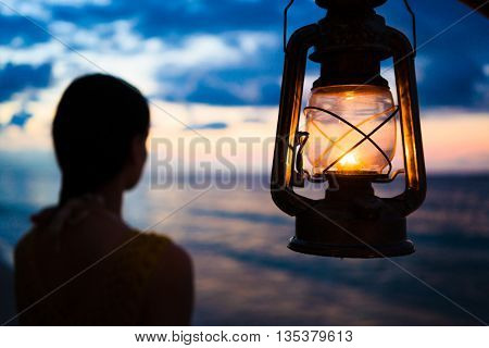 Woman in lantern shine looking to sea at sunset