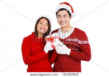 Portrait of young couple in christmas attire holding gift on white background