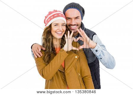 Happy young couple making heart gesture on white background