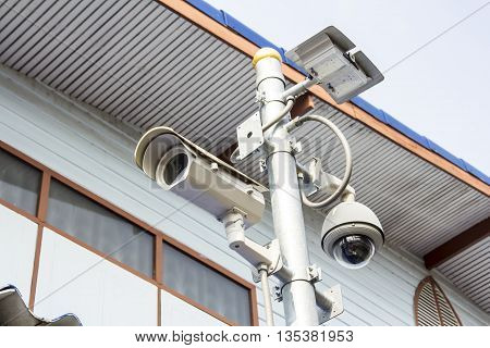 CCTV surveillance camera on the post with wall background for safety concept. poster